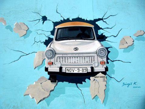 Graffiti de un coche atravesando una pared